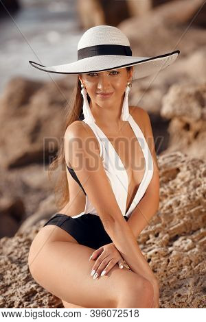 Elegant Fashionable Woman In White Hat And Sexy Swimsuit Posing On The Beach. Happy Smiling Girl Mod