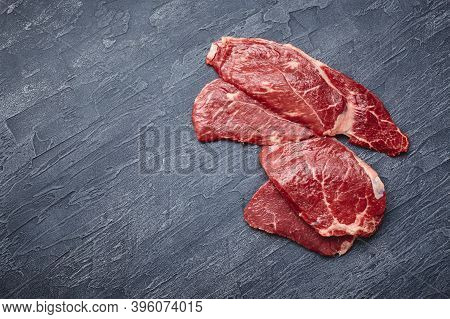 Four Raw Ribeye Steak On A Black Background. View From Above