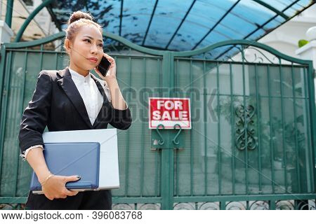 Female Vietnamese Real Estate Agent With Documents In Hands Standing At Gates Of House On Sale And T