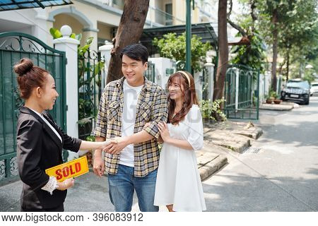 Happy Young Vietnamese Couple Buying Their First House With Help Of Estate Agent