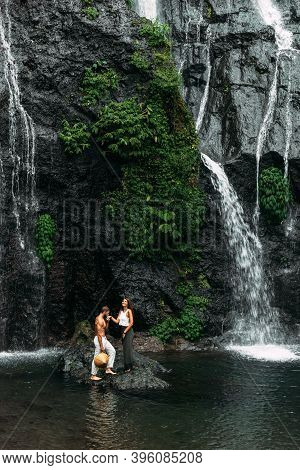 A Man Proposes To A Woman At A Waterfall. A Guy Proposes To A Girl In Bali. Offer Of A Hand In Trave