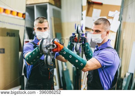 Glazier worker in face mask holding glass in workshop. Industry during coronavirus Covid-19