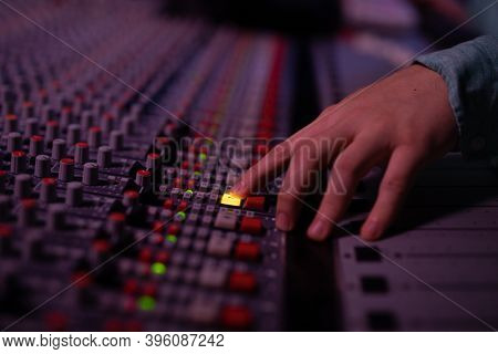 Close up of the hand of a young Caucasian male sound engineer selecting a channel on a mixing desk in a recording studio