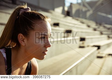Side view close up of a Caucasian female athlete practicing at a sports stadium, focusing before a race. Track and Field Sports Training in Stadium.