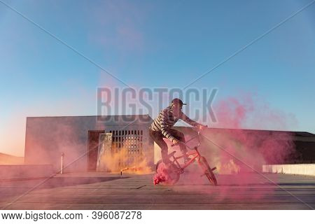 Side view of a young Caucasian man riding a BMX bike and doing tricks on the rooftop of an abandoned warehouse, with a pink smoke grenade attached to the bike