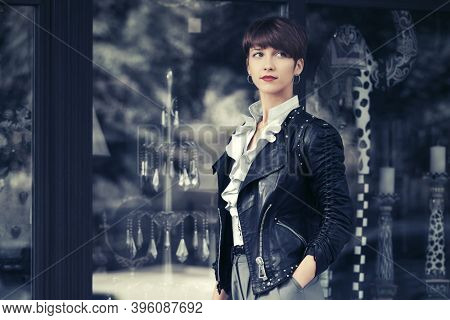 Young fashion woman walking on city street Stylish female model in black leather jacket with pixie hair style