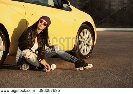Young fashion hipster woman sitting on sidewalk leaning on car  Stylish female model in black leather jacket purple beanie and ripped jeans