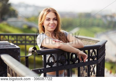 Happy young woman leaning on railing Stylish fashion model with long straight hair in gray t-shirt