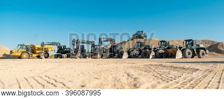 Diggers, excavators and other heavy machines in mine of quarry standing in line