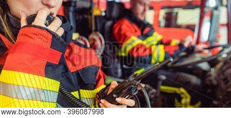 Fire fighter woman on duty using the radio in the fire truck
