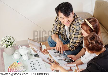 Happy Young Vietnamese Couple Looking At Apartment Photos And Talking To Real Estate Agent