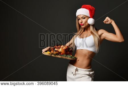 Young Beautiful Sexy Blonde Fitness Woman In White Clothes And Santa Hat Standing With Roasted Chick