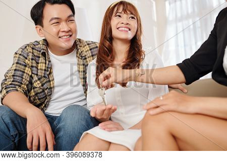 Happy Young Beautiful Vietnamese Couple Looking At Real Estate Agent Giving House Keys