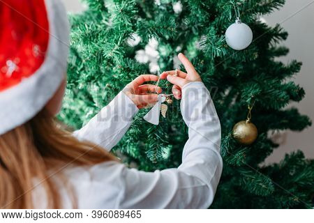 A Fair-haired Schoolgirl Decorates An Artificial Christmas Tree In A Santa Hat With Christmas Decora