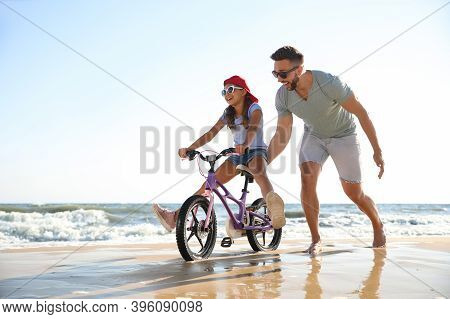 Happy Father Teaching Daughter To Ride Bicycle On Sandy Beach Near Sea