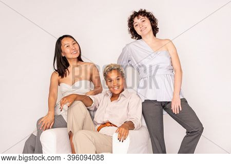 Happy young African woman in white casualwear sitting in comfortable leather armchair surrounded by her Caucasian and Asian friends