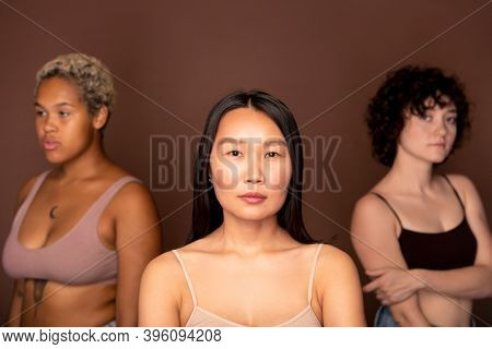 Young serious Asian woman in beige tanktop standing in front of camera against two other females of various ethnicities and looking at you