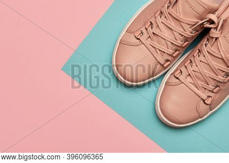 Stylish Pink Female Shoes On Pastel Background, Copy Space. New Sneakers On Pink And Blue Background