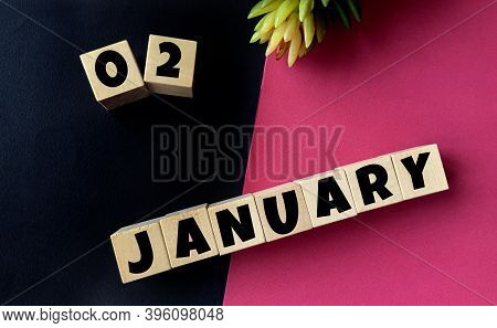 January 2 On Wooden Cubes On A Black And Pink Background.beginning Of Year .calendar For January.