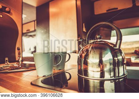 Shiny Metal Water Kettle And Two Cups With Hot Tea Inside Rv Camper Van Kitchen Area. Recreational V