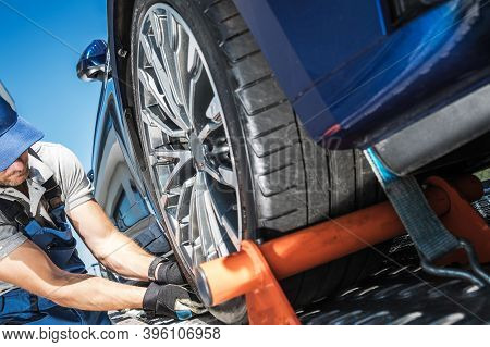 Caucasian Towing Truck Driver Securing Vehicle Cargo. Modern Car Towed Away. Repo Men Concept.