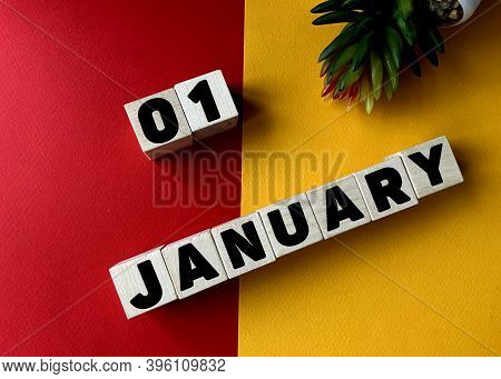 January 1 In Black Letters On Wooden Blocks On A Divided Yellow-red Background .next To A Flower .ca