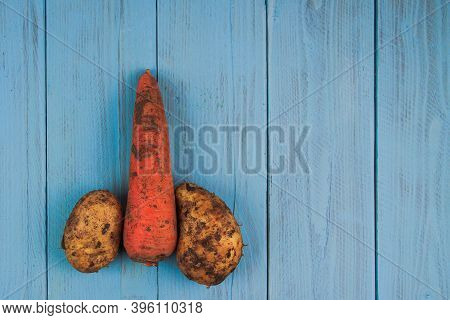 Carrot With Potatoes Arranged In The Shape Of A Penis On A Blue Board. Concept Of Sex, Erection, Pot