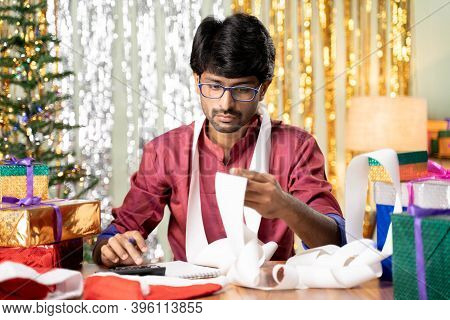 Young Man Busy In Calculating Holyday Expenses After Christmas Or New Year 2021 Holiday Celebration