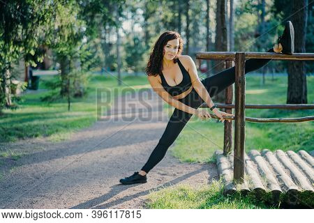 Flexible Young Curly Woman Wears Black Top Leggings And Sneakers, Stretches Legs, Does Sport During