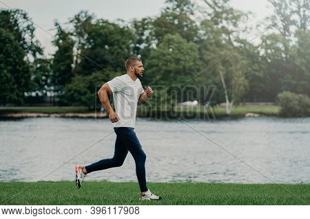 Athlete Bearded Man Runs Along Beautiful Landscape, Demonstrates Endurance, Dressed In Active Wear,