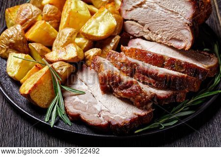 Whole Roasted Pork Loin Served With Baked Potato Wedges, Rosemary  On A Black Plate On A Dark Wooden