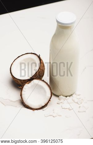 Bottle Of Coconut Milk Near Halves And Flakes On White Surface Isolated On Black