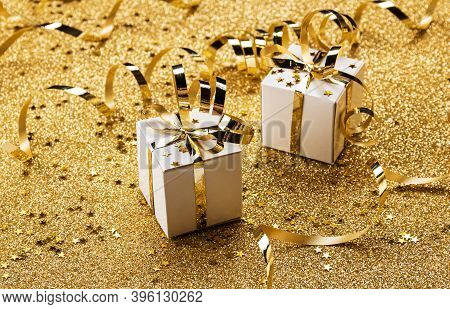 Two Bright Christmas Gifts On A Gold Background With Serpentine, Tinsel And Confetti