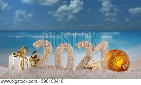 Festive Lettering 2021, Gift With Golden Ribbon, Christmas Ball And Starfish In The Sand On The Beac