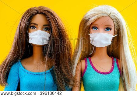 Tambov, Russian Federation - June 12, 2020 Two Barbie Dolls With Medical Masks. Yellow Background.