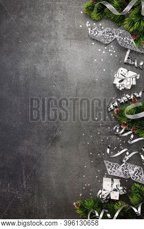 Christmas Tinsel, Serpentine, Silver Ribbon And Christmas Gifts On A Dark Background