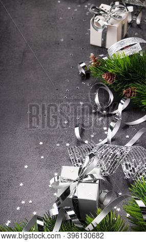 New Year Concept. Bright Christmas Gift With Silver Ribbon Close Up, Fir Tree And Stars Confetti