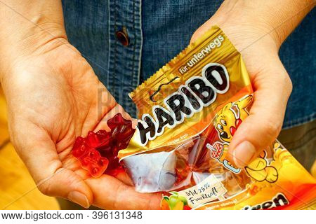 Tambov, Russian Federation - October 30, 2020 Woman Pouring Haribo Gummy Bears Candy  From Haribo Pa