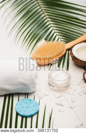 Coconut Half, Cosmetic Cream, Towel, Massage Brush And Sponge Near Palm Leaves On White