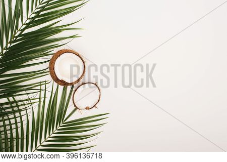Top View Of Coconut Halves Near Palm Leaves On White Background With Copy Space