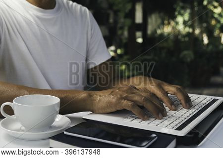 A Man Working At Home And Using Laptop On The Table. Technology And Business Concept.