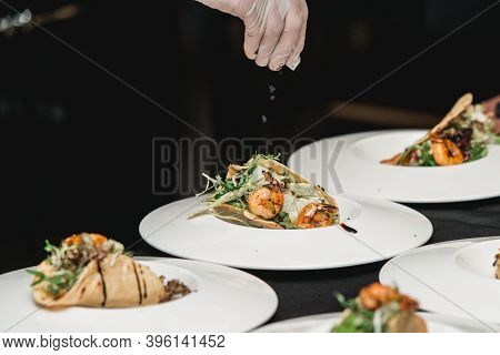The Chef At The Restaurant Making Shrimp Tacos With Coleslaw And Salsa