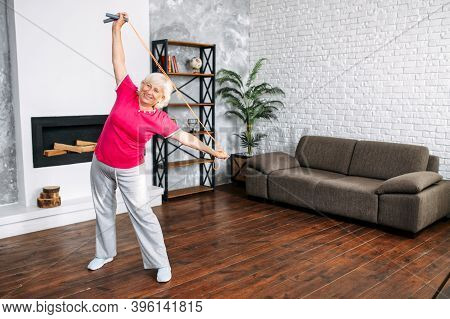 Cheerful And Active Senior Grey-haired Woman Doing Stretching Exercise At Home. A Grandmother In Spo