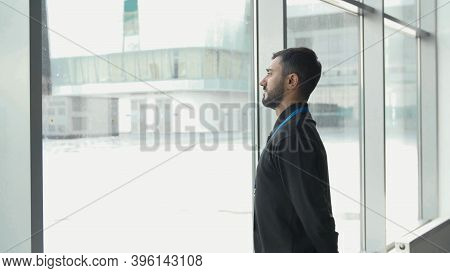 Office Worker Looks At Snow. Media. Businessman Frowns At Falling Snow Through Panoramic Windows. Of