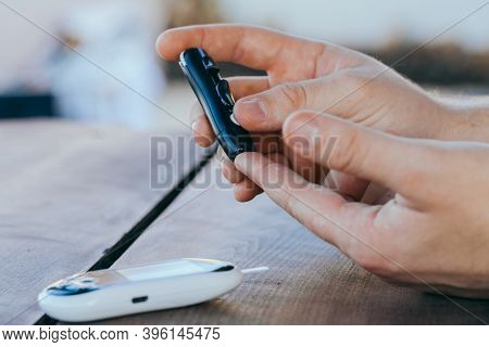 Man Taking A Blood Sample With A Lancet Handle Outside Against The Backdrop Of Greenery. Diabetes, H