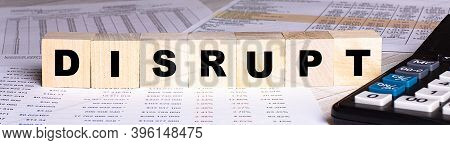The Word Disrupt Is Written On Wooden Cubes Near The Graphs And Calculator.