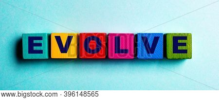 The Word Evolve Is Written On Multicolored Bright Wooden Cubes On A Light Blue Background