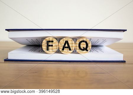 Concept Word 'faq, Frequently Asked Questions' On Wooden Circles Between Pages Of A Book On A Beauti