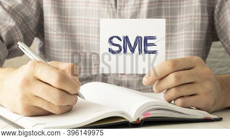 Hand With Pen Pointing To Sme , Or Small And Medium Enterprises, Sign On The Paper