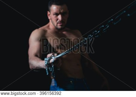 Guy On Black With Strained Muscles Holds A Rusty Metal Chain, A Concept Of Strength Man Power